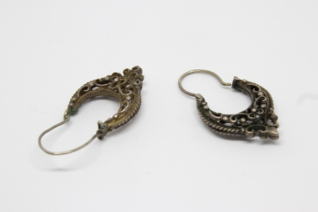 a pair of antique silver earrings closeup. photo has taken with photobox with white background.