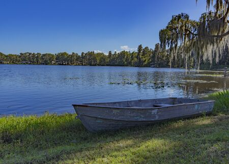 A rowboat is perched on the shore of a small lake in Florida