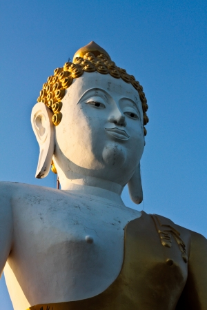 Stucco Buddha statue with blue sky background,     Large Buddha Statue made out of plaster by skilled local technicians is to remind people to do good and help another human being, Enshrined in Chiang Mai, Northern Thailand  Stock Photo