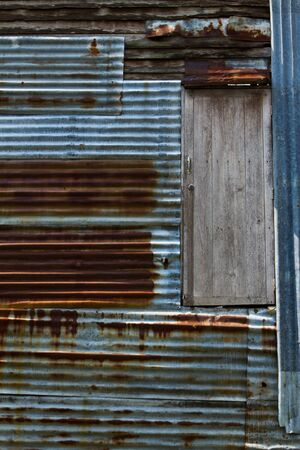 Old wooden door with rusty zinc wall,  Rusty old corrugated iron walls of the overlapping disorder whit wooden doors that open to the outside in the sun to light shade and aesthetic dimension, A dramatic scene, Chonburi in Thailand