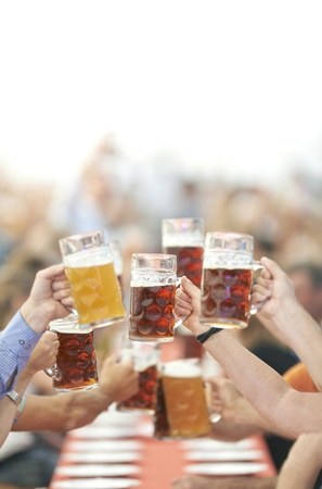 beer fest: Oktoberfest beer drinkers raise glass Stock Photo