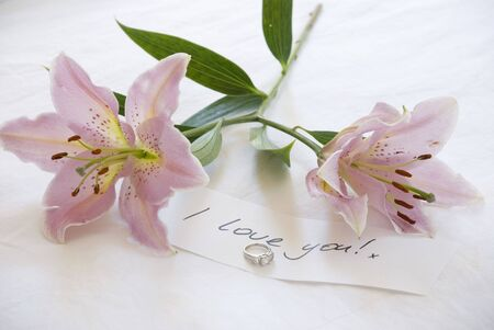 declaring: two beautiful lillies lie on the bed by a diamond engagament ring and note declaring love. Stock Photo