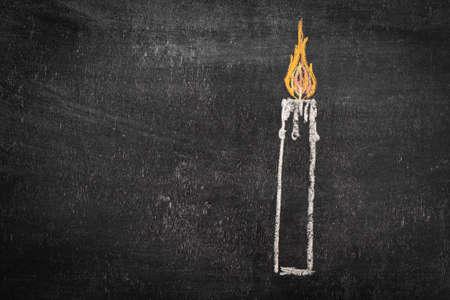 A burning candle drawn on a chalkboard