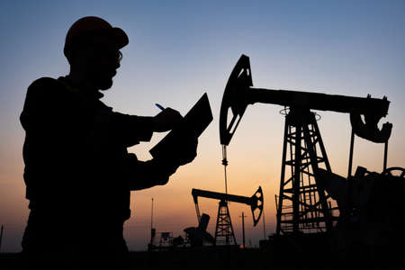 Oil worker checks an oil rig at sunset. Maintenance of oil pump jacks 免版税图像
