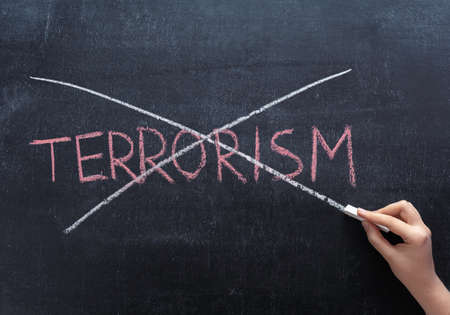 The teacher's hand crosses out the word TERRORISM on the chalkboard