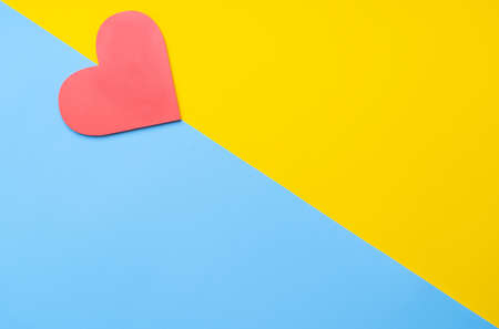 Red heart symbol on yellow-blue paper background. Cope-space