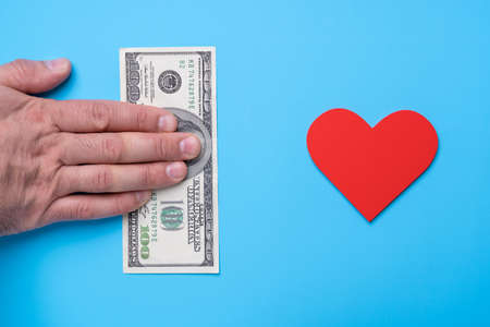Man's hand with a 100 dollar bill holds out money towards a red heart on a blue background
