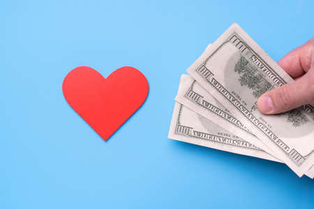Man's hand with dollars stretches out his hand to a red heart on a blue background, Donate