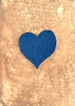 Jeans heart on aged paper photo