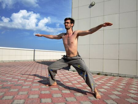 Young man doing exercises on the top of skyscraper photo