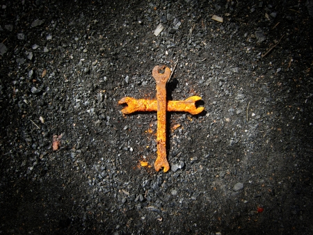 iron cross: Rusty wrench cross on the coal background Stock Photo