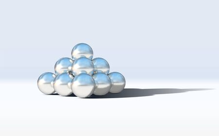 Chrome metal balls in pyramid stack on abstract calm and relaxing white background
