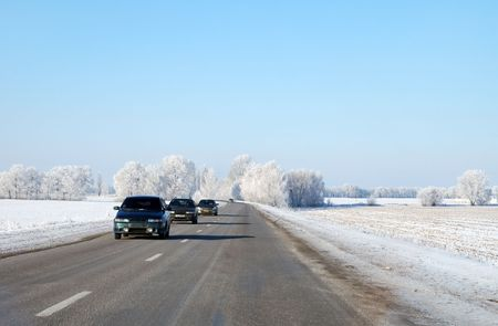 Three cars driving on a winter road