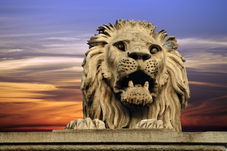 Lion statue from Budapest bridge on bright sky