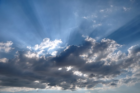 wheather: The Sun rays going through dark clouds Stock Photo
