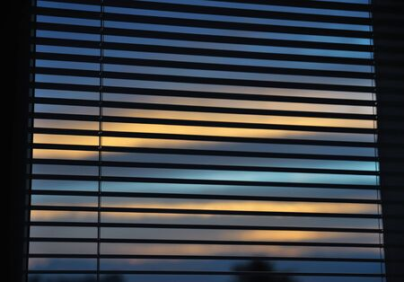 Venetian blinds on the window and dusk behind photo