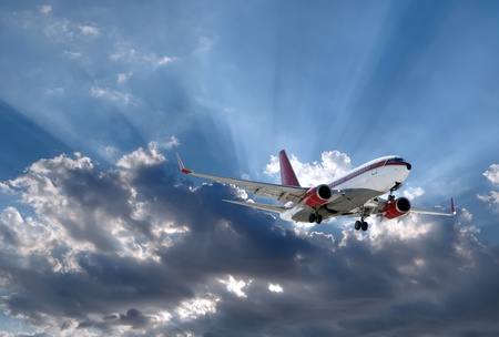 a plane above Sun rays going through dark clouds Stock Photo - 13595004