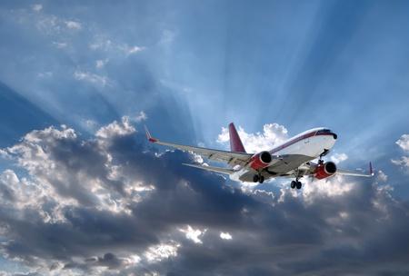 a plane above Sun rays going through dark clouds photo