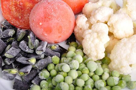 heap of frozen tomato, asparagus, peas and cauliflower photo