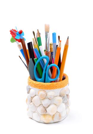 pencils, brushes, plastic knife, scissors in handmade pencil-box isolated photo