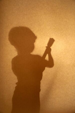 boy playing guitar: sepia silhouette of a boy playing guitar Stock Photo