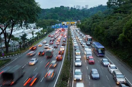 in row: Tráfico de la tarde en la carretera de conducción a la izquierda en Malasia