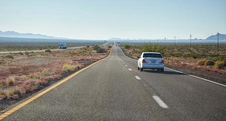 White car on highway in Nevada desert Stock Photo