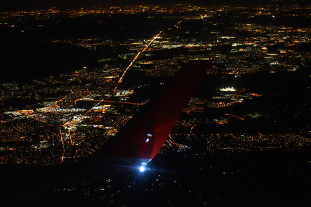 View of night city under the wing of airplane flying high