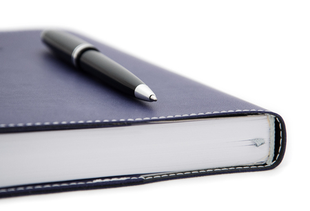 close-up view of tip of ballpoint pen laying on the notebook