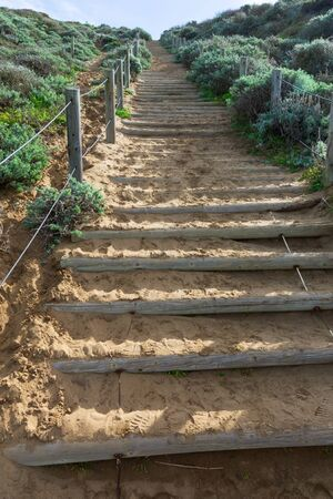 Stairway to ocean beach in Sanfrancisco made on sandy hill with thick wooden logs. Banco de Imagens