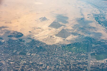 The Giza pyramid complex, also called the Giza Necropolis viewed from airplane window. Khufu, Khafre, Menkaure and Sphinx are visible. Stock Photo