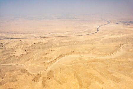 Rad and power lines on a desert landscape of Egypt