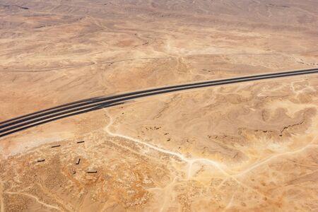 Lonely truck moves on black line of a road in Sahara desert Stock fotó