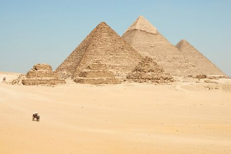 Horse drawn carts near Giza pyramids. Khufu, Khafre, Menkaure and pyramids Queens are seen from desert.