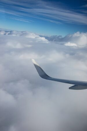 Wing of airplane above clouds made from window Stock Photo