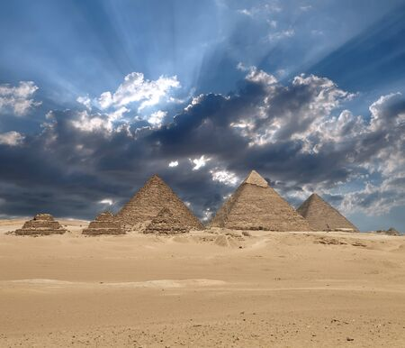 Sun shines from clouds above the Giza pyramid complex or the Giza Necropolis on the Giza Plateau in Egypt near Cairo includes the Great Pyramid of Giza the Pyramid of Khafre and the Pyramid of Menkaure. Composite image. Stockfoto