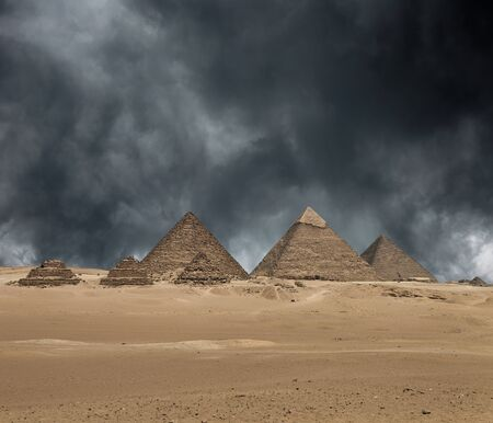 The Giza pyramid complex, or the Giza Necropolis on the Giza Plateau in Egypt near Cairo includes the Great Pyramid of Giza the Pyramid of Khafre and the Pyramid of Menkaure under dramatic grey stormy sky. Composite image.