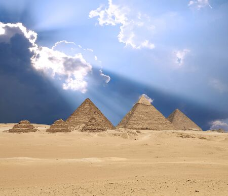 Sun shines from clouds above the Giza pyramid complex or the Giza Necropolis on the Giza Plateau in Egypt near Cairo includes the Great Pyramid of Giza the Pyramid of Khafre and the Pyramid of Menkaure. Composite image. Stock Photo