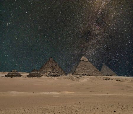 The Giza pyramid complex, or the Giza Necropolis on the Giza Plateau in Egypt near Cairo includes the Great Pyramid of Giza the Pyramid of Khafre and the Pyramid of Menkaure under night starry sky. Composite image.