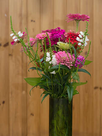 Bouquet of different color zinnia flowers in a glass vase