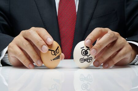 Bullying concept in workplace with angry and afraid eggs character controlled by executive hand  photo