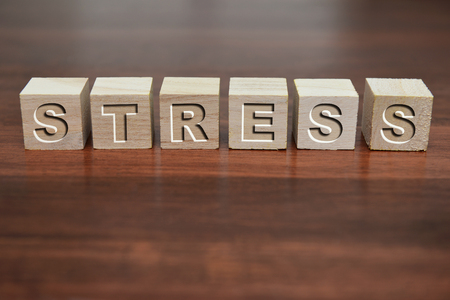 defocussed: Word Stress written on wooden cube against a defocussed background.