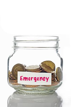 Las monedas de oro en el frasco con la etiqueta de emergencia aisladas en el fondo blanco Foto de archivo