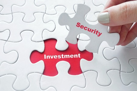 investment security: Close up of girls hand placing the last jigsaw puzzle piece with word Investment and Security as Investment Security concept Stock Photo