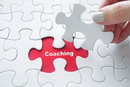 interpersonal: Close up of girls hand placing the last jigsaw puzzle piece with word Coaching as business concept Stock Photo