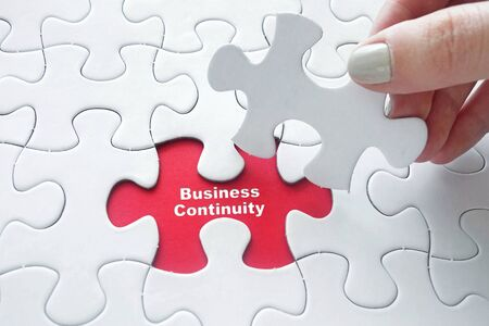 business continuity: Close up of girls hand placing the last jigsaw puzzle piece with word Business Continuity Stock Photo