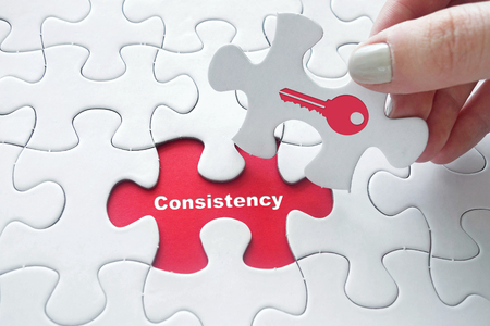 consistency: Close up of girls hand placing the last jigsaw puzzle piece with Consistency is the key concept Stock Photo