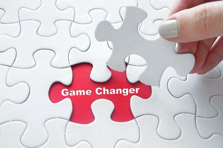 Close up of girl's hand placing the last jigsaw puzzle piece with word Game Changer as business concept