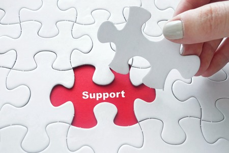 growing partnership: Close up of girls hand placing the last jigsaw puzzle piece with word Support as business concept Stock Photo