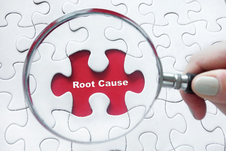 Word Root Cause with hand holding magnifying glass over jigsaw puzzle